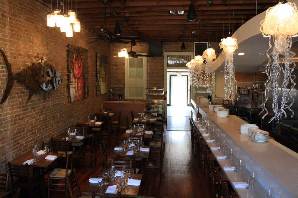 The interior of Starfish with its historic brick walls, glass jellyfish lights, vibrant art and fish sculpture.