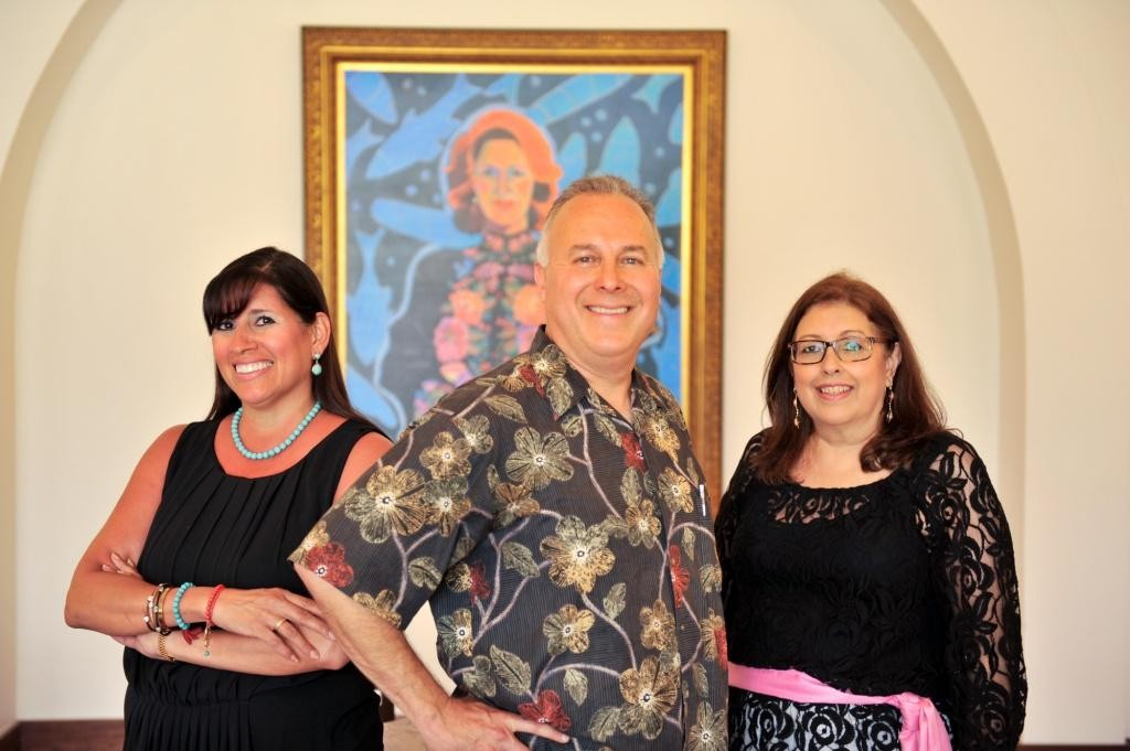 From left: Diana, Louis, and Teresa in front of a portrait of their mother, Viola. Image courtesy of mysanantonio.com