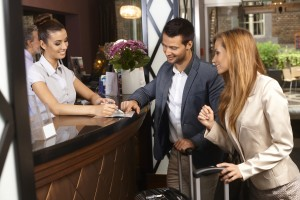 Receptionist giving tourist information to hotel guests upon arr