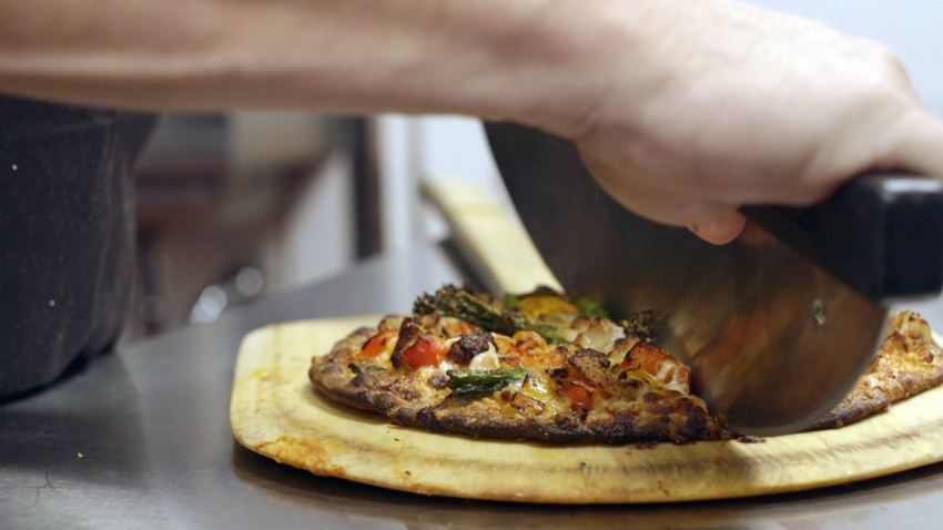 Slicing fresh baked pizza pulled from the oven.