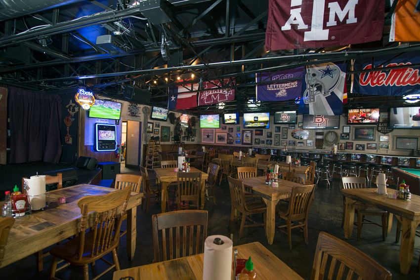 Inside the lively Fred's TCU, college flags and televisions create a festive ambiance.