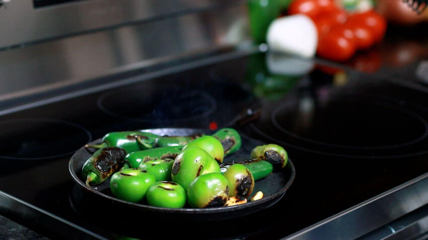 Roast tomatillos, jalapeño peppers, and garlic clove on a grill.