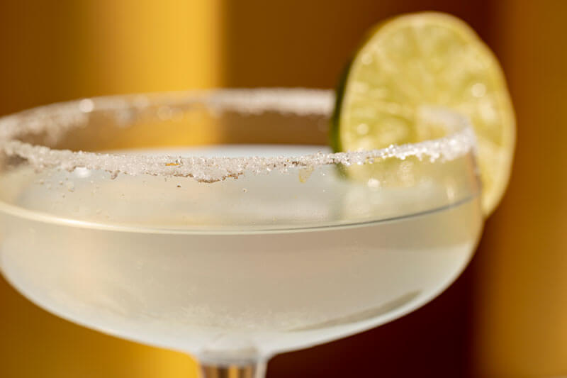 Close up of margarita cocktail with salted rim and lime