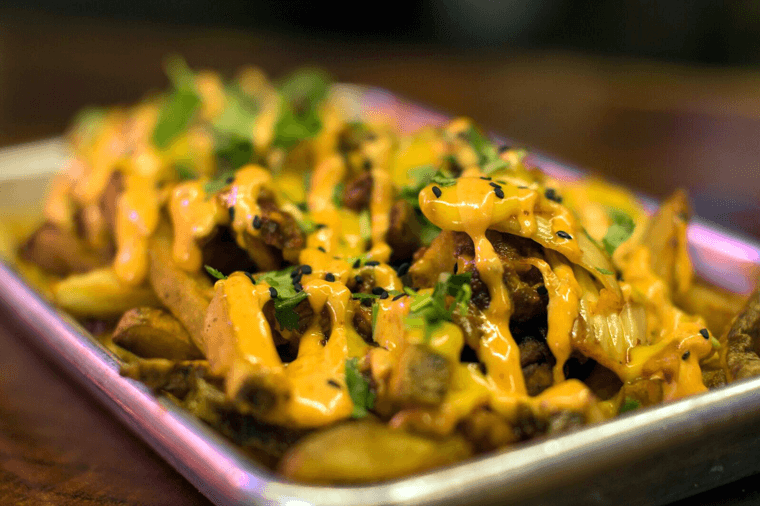 The house-favorite kimchi fries are made with sautéed kimchi, marinated beef, cheese, cilantro, and Benchwarmers' special spicy sauce.