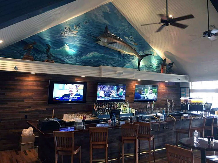 The bar at Trout Street features reclaimed wood and a colorful ocean mural. Photo via MySA.com.